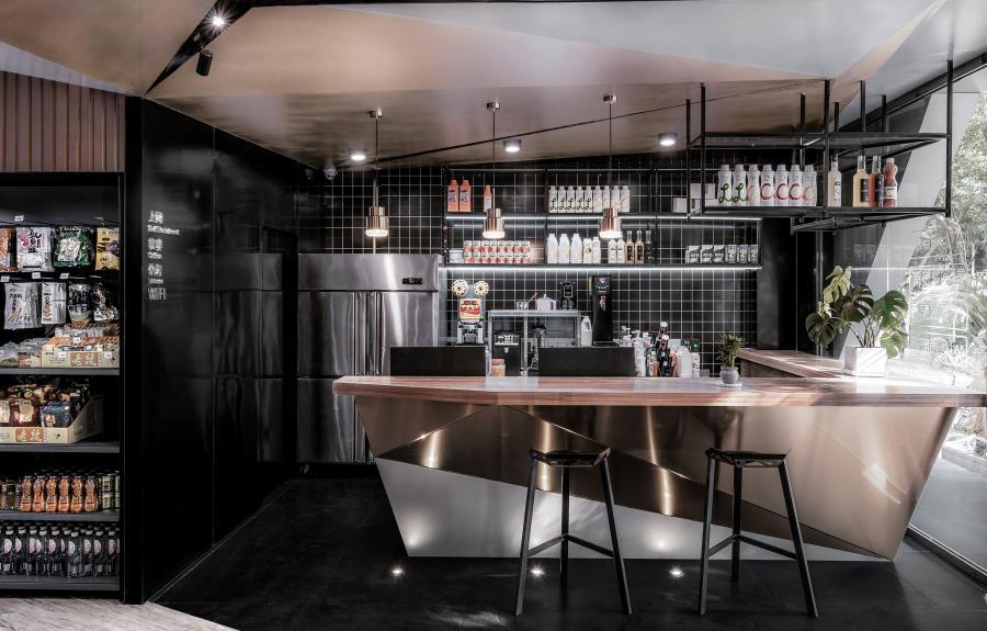 前厅延续了同样的元素,运用大块面的异型三角和黑白金的色系搭配,色感和体块之间的穿插,将未来感故事延伸,把墙面和天花巧妙的联合一起,让人仿佛置身与山洞之中,在特殊的空间感受非一般的空间尺度与色感。 置身咖啡前区,酷炫的洞穴感与另类的吧台设计亮点,来杯咖啡或奶茶,享受整个下午的休闲时光,让电竞的激烈过程稍微放松下来。
