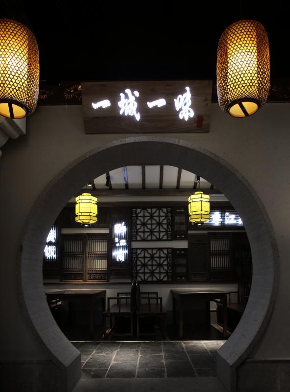 """""""楼阁宜佳客""""——南方建筑因气候炎热潮湿,所以一般以二层楼房居多,底层是砖结构,上层是木结构。此次门头的设计,便是借鉴了这一特点,一楼以外墙漆搭配石材及黑色不锈钢,带有宝瓶造型的玻璃门加上外墙大面积的玻璃设计,即使站在门外也可以感受到餐厅的气氛;二楼便是用木结构造型,营造楼阁的氛围,,搭配窗外绿植更添色彩。"""