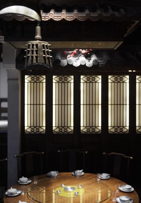 江南多雨,屋瓦在建筑中既起了装饰又有挡雨之用,设计中将此元素提出,并融入水景之中,低矮砖墙便体现屋檐延绵之感。 云朵灯飘散于顶,对面的三个连亭的用餐