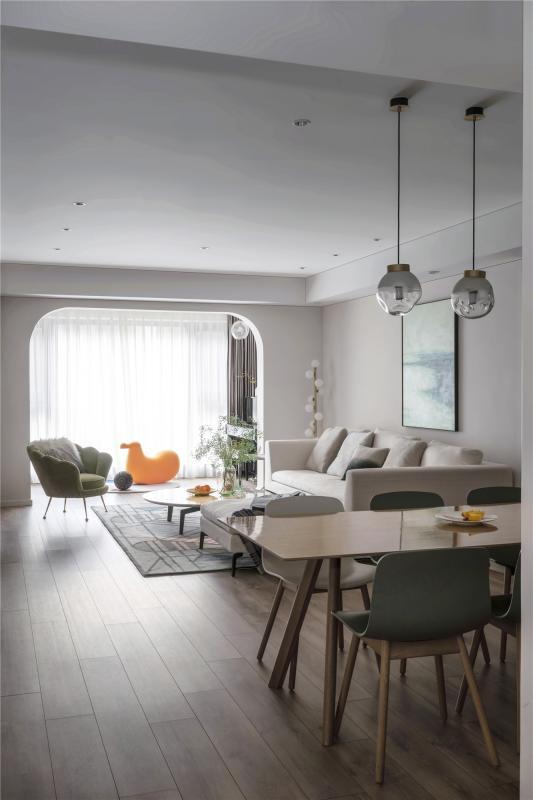 进门入户,屋外的阳光透过落地玻璃洒落房间,白色的墙壁和浅色的家具映衬在一起,简洁明亮。为了提升整体空间亮度,我们将客餐厅打通成为一体,从暗到亮,层次渐进。