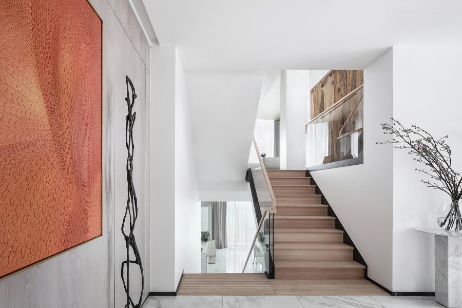 """门厅处的橙色版画以热烈的姿态迎接着来访者,它是整个空间中色彩的燃点。用自己耀眼的明丽中和着灰调的沉滞,宛若尼采笔下的""""酒神狂欢""""。"""