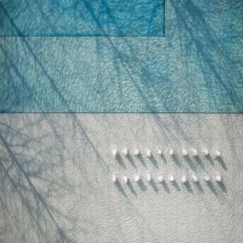 """4米高的景墙塑起建筑的入口礼序,高耸的乔木挺拔俊俏,静水倒映着蔚蓝的天,风拂过便荡开一圈圈的涟漪。这里的建筑、景观及至室内,均是当代简雅的视像表现,正如""""古翠隐秀""""的名字一般,隐于闹市,自然灵秀。"""