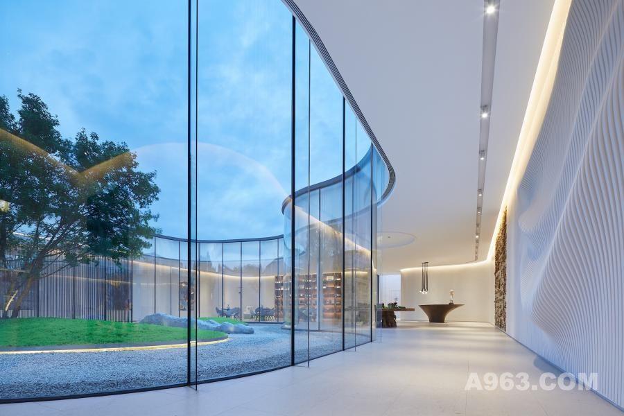 橡树珑湾生活美学体验馆就是如此,设计师打破了传统售楼处的固有规则,跨越了建筑、景观、空间三者的边界,又借用流线型的曲线,流水式的分离汇聚将三者的边界渗透融合,创造出了新的可能性。